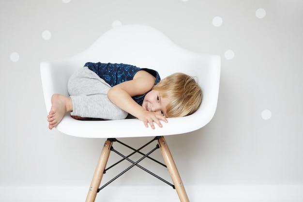 Glückliche sorglose kindheit. süßes kaukasisches kind, das sich in einem weißen designerstuhl aufrollt und sich vor seinen freunden versteckt, während es verstecken spielt. netter junge, der spaß drinnen hat.