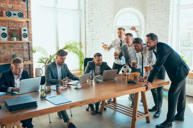 Glückliche sorglose kollegen, die spaß im büro haben, während ihre mitarbeiter hart und hoch konzentriert arbeiten.