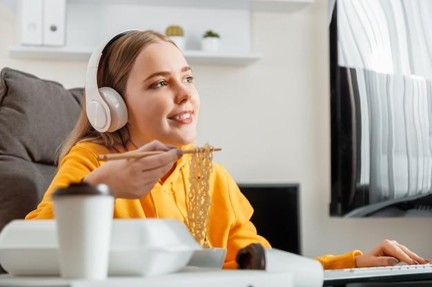 Glückliche spielerin isst nudeln mit essstäbchen chinesisches gericht zu hause mit desktop-pc-computer während des streaming-videospiels. frau teenager-mädchen leidenschaftlich arbeiten programmierung.