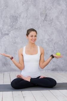 Glückliche sportfrau, die apfel hält auf einer yogamatte hält