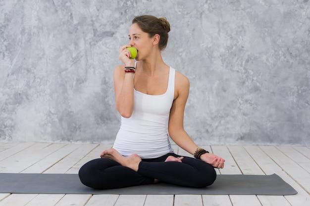 Glückliche sportfrau, die apfel sitzt auf einer yogamatte isst