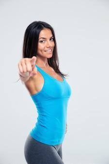 Glückliche sportfrau, die finger auf kamera zeigt