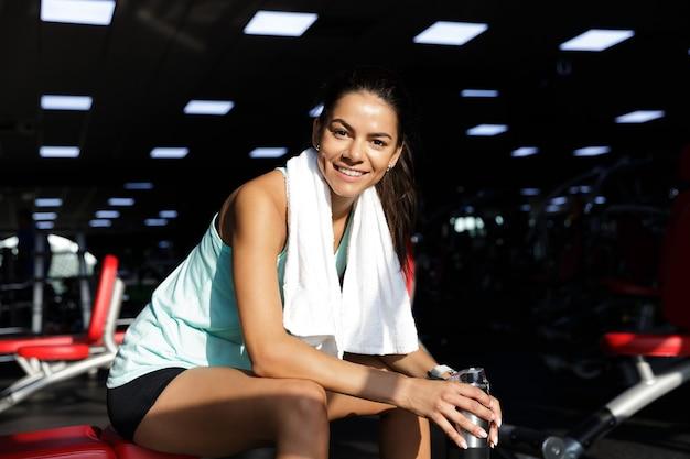 Glückliche sportlerin, die die kamera beim entspannen auf bank im fitnessstudio betrachtet