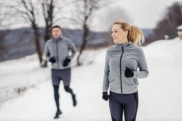 Glückliche sportlerin, die im winter mit ihrem freund auf der show in der natur läuft. winterfitness, marathon, cardio