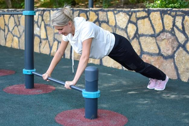 Glückliche sportlerin im fitnessstudio im freien. frau auf einem sporttrainer auf sportplatz. sport für die gesundheit.
