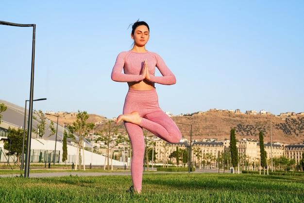 Glückliche sportliche frau, die yoga im freien praktiziert