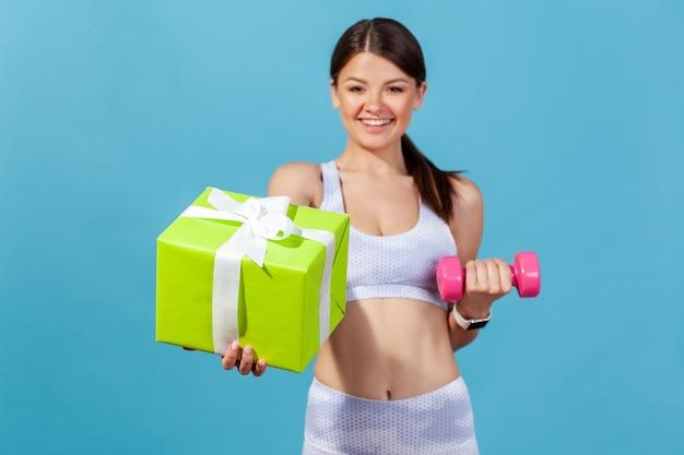 Glückliche sportliche frau in weißer sportkleidung mit grüner geschenkbox und rosa hantel
