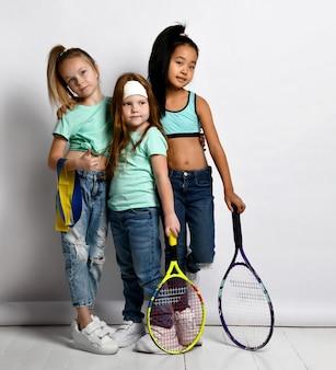 Glückliche sportliche kinder genießen training und gesunden lebensstil. kleine mädchen in jeans, sportliche t-shirts mit wasserflasche, großer tennisschläger, fitnessgummi mit daumen nach oben. isolierte studioaufnahme