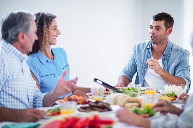 Glückliche sprechende familie beim frühstücken