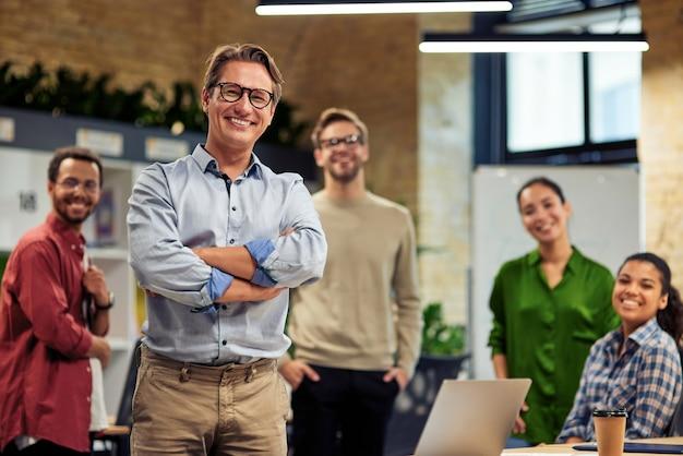 Glückliche startup-teamgruppe fröhlicher, gemischtrassiger geschäftsleute, die beim stehen in die kamera lächeln