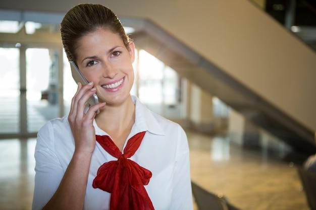 Glückliche stewardess, die auf ihrem handy spricht