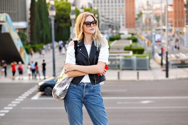 Glückliche stilvolle blonde frau, die auf der straße aufwirft, jeans und lederweste trägt