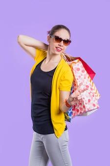 Glückliche stilvolle frau, die friedenszeichen beim halten der schönen einkaufstasche zeigt