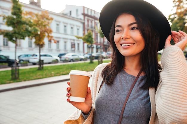Glückliche stilvolle frau, die kaffeetasse hält