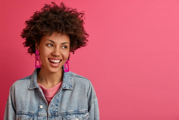 Glückliche stilvolle frau mit afro-frisur schaut zur seite, lächelt positiv, genießt das leben, amüsiert sich von jemandem, trägt jeansjacke posiert drinnen gegen rosige wandleerstellen für ihre werbung