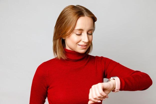 Glückliche stilvolle geschäftsfrau im roten rollkragenpullover, der smartwatch auf ihrem handgelenk betrachtet, nachricht auf dem bildschirm prüfend, die zeit prüfend. auf grauer oberfläche isoliert