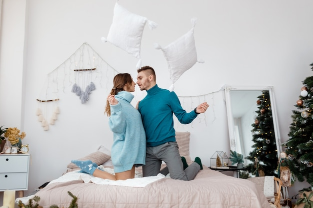 Glückliche stilvolle liebevolle paare, die eine kissenschlacht im bett haben. junger mann und frau erwartet baby für weihnachten. tiefenschärfe