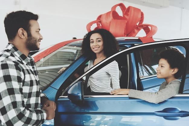 Glückliche stolze afro-frau erhielt neues luxuriöses auto
