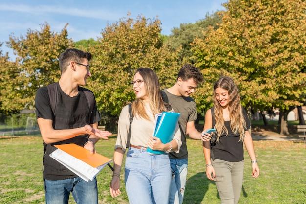 Glückliche studenten an tragenden büchern des parks und am haben des spaßes