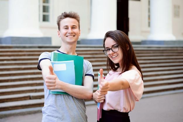 Glückliche studenten, die daumen oben außerhalb eines universitätsgeländes zeigen