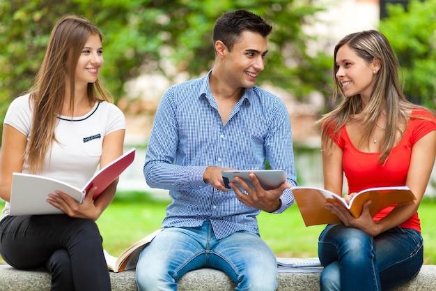 Glückliche studenten, die im freien studieren