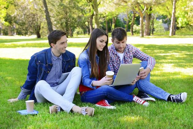 Glückliche studenten, die im park sitzen