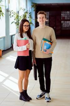 Glückliche studenten im korridor der universität am sonnigen tag mit den buchordnern und kursbüchern bereit, stark zu studieren und hohe ergebnisse zu erzielen