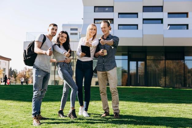 Glückliche studenten mit büchern gehen auf den grünen rasen vor der bibliothek