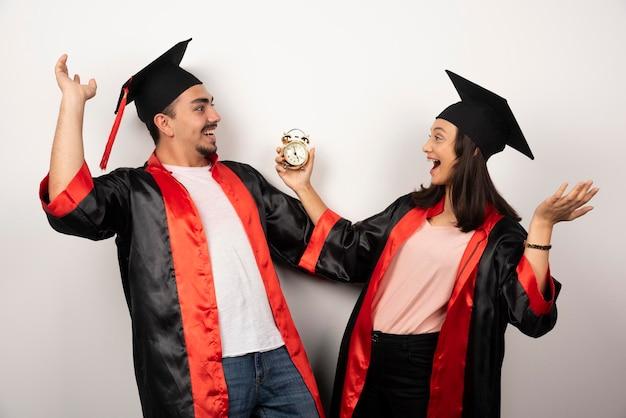 Glückliche studenten mit uhr, die abschluss auf weiß feiert.