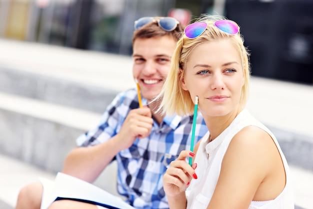 Glückliche studenten sitzen auf treppen auf dem campus