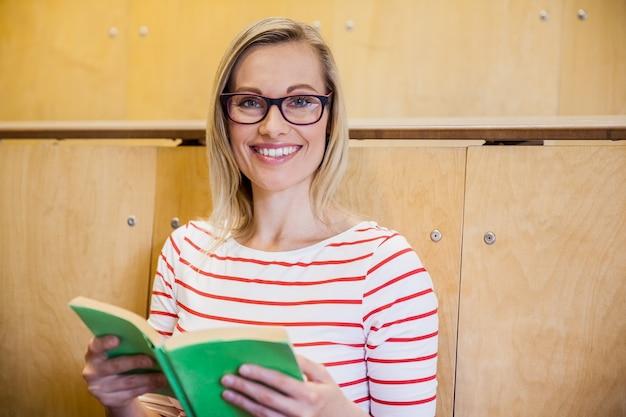 Glückliche studentin, die ein buch an der universität liest