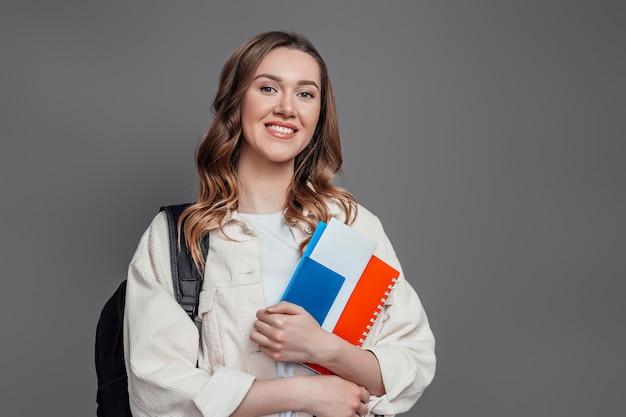 Glückliche studentin, die rucksackbuchnotizbuchpass lokalisiert auf einem dunkelgrauen wandeinwanderungspapier hält