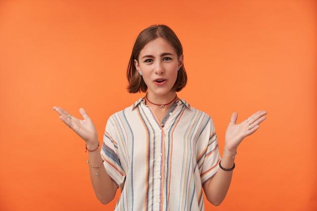Glückliche studentin hört gute nachrichten und zeigt freude, trägt rote halskette und viele armbänder, mit weit geöffneten armen gegen orange wand. jugendliche und emotionales konzept