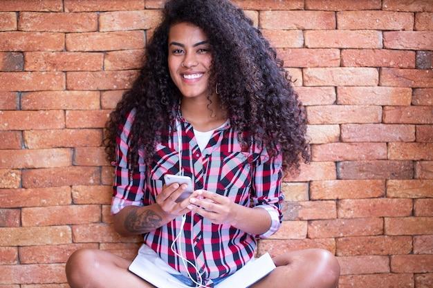 Glückliche studentin mit afro-frisur, die mit backsteinmauerhintergrund unter verwendung des handys sitzt und lächelt.