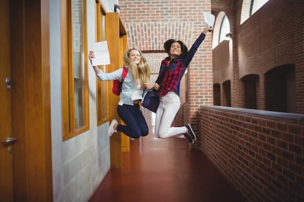 Glückliche studentinnen, die ergebnisse an der universität erhalten