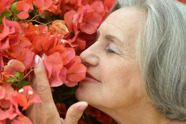 Glückliche süße ältere frau mit rosa blumen