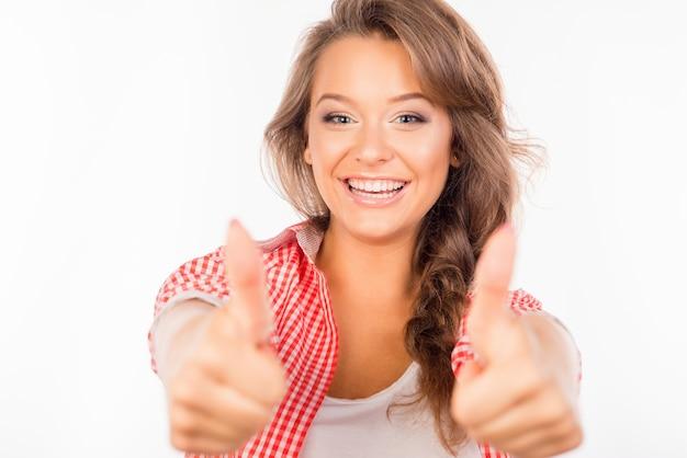 Glückliche süße frau, die daumen oben zeigt und lächelt