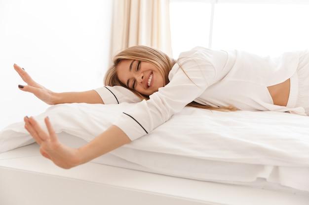 Glückliche süße frau im pyjama, die ihre arme ausstreckt und lächelt, während sie nach dem schlafen auf dem bett liegt