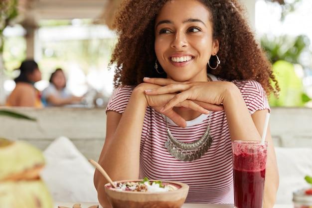 Glückliche süße frau mit dunkler haut, afro-frisur, schaut mit fröhlichem ausdruck weg, hält hände unter dem kinn, isst köstliches exotisches dessert und trinkt cocktail, träumt von etwas angenehmem