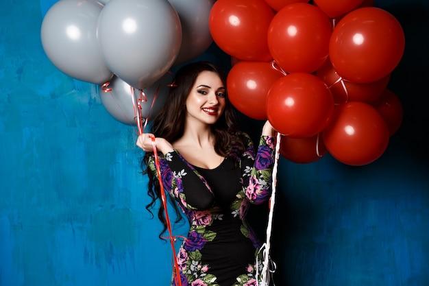 Glückliche süße frau mit luftballons. mädchen, das spaß hat und lacht, schönes langes haar und luxus-make-up