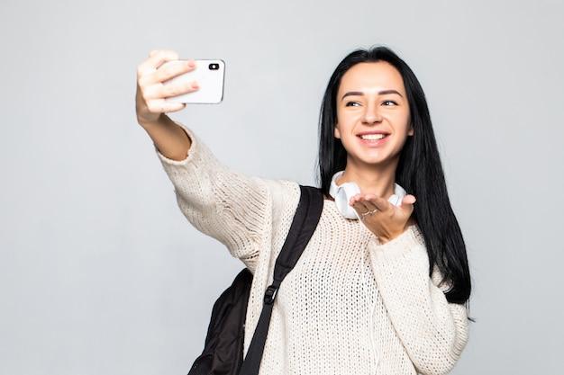 Glückliche süße junge frau, die luftkuss sendet und selfie mit smartphone über graue wand nimmt