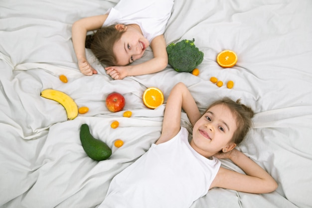 Glückliche süße kinder spielen mit obst und gemüse. gesundes essen für kinder.