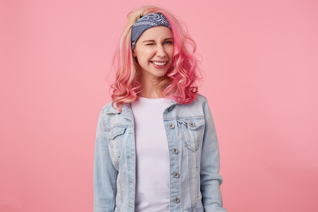 Glückliche süße lächelnde dame mit rosa haaren und tätowierten händen, die caera betrachtend und zwinkernd, stehend, ein weißes t-shirt und eine jeansjacke tragend.