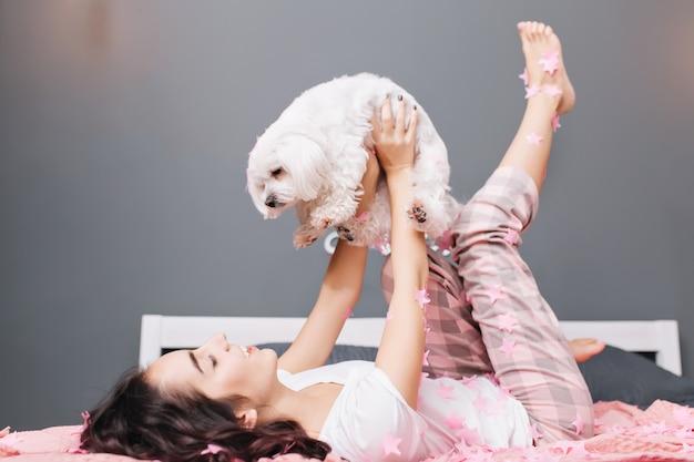 Glückliche süße momente der jungen schönen frau im pyjama mit geschnittenem brünettem lockigem haar, das spaß mit hund auf bett in der modernen wohnung hat. lächeln, entspannung in rosa lametta, gemütlichkeit zu hause