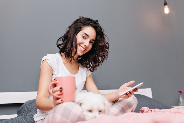 Glückliche süße momente der jungen schönen frau mit geschnittenem brünettem lockigem haar im schlafanzug, der auf bett mit hund in der modernen wohnung kühlt. lächeln, im internet surfen, gemütlich zu hause entspannen