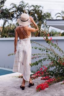Glückliche süße romantische kaukasische frau im sommer elegantes weißes kleid mit offenem rücken, strohhut