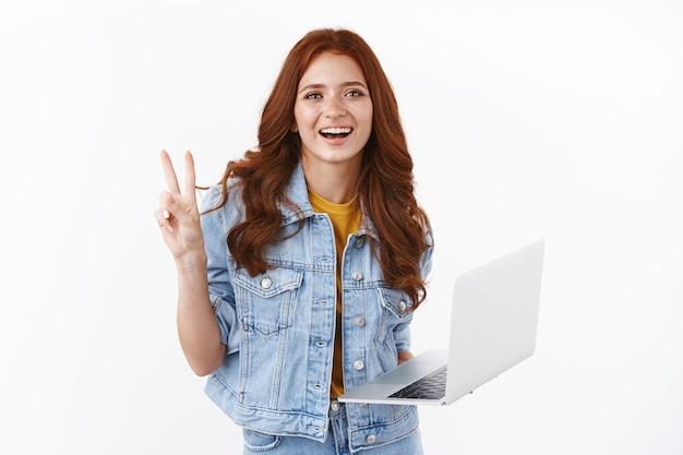 Glückliche süße rothaarige freiberuflerin in jeansjacke erreicht leicht das ziel mit dem laptop, zeigt den friedenssieg, das zeichen des guten willens, lächelt freudig, arbeitet an der fernbedienung, bereitet das projekt vor, weiße wand