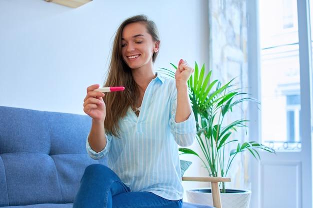 Glückliche süße zufriedene junge lächelnde frau freut sich über ein positives schwangerschaftstestergebnis