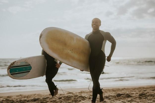 Glückliche surfer, die am strand laufen