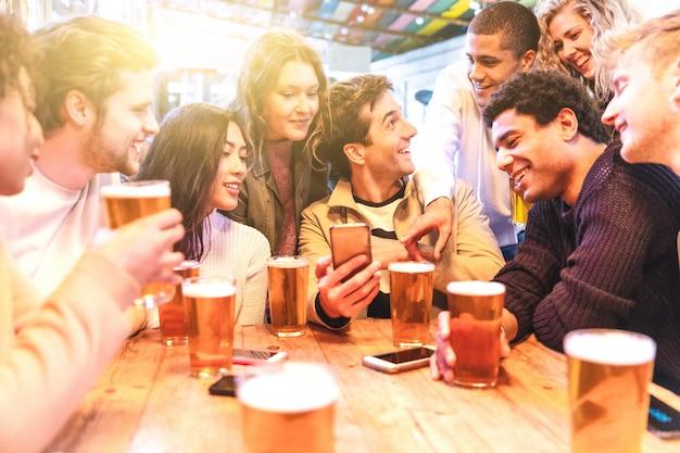 Glückliche tausendjährige freunde an trinkendem bier der kneipe